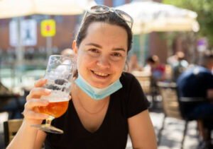 Woman in protective medical mask with glass of beer at a street bar
