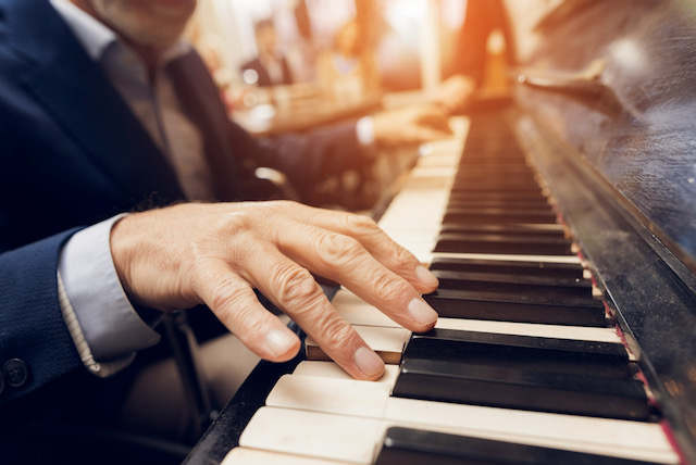 Man plays piano after working with an occupational therapist