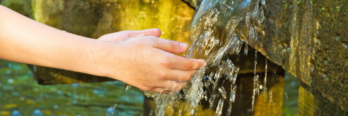 Kind beim Hände waschen an einem Brunnen