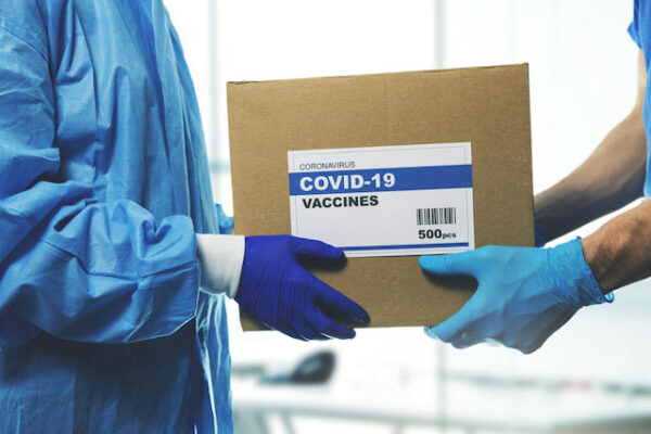 medical worker accepting delivery of covid-19 vaccines from delivery man