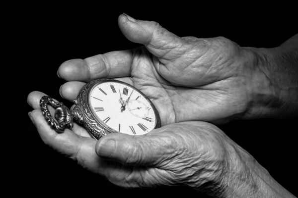 Senior woman hands holding ancient clock. Aging problems, senior age and stream of time theme.