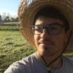 Eric Gratta headshot wearing a straw hat