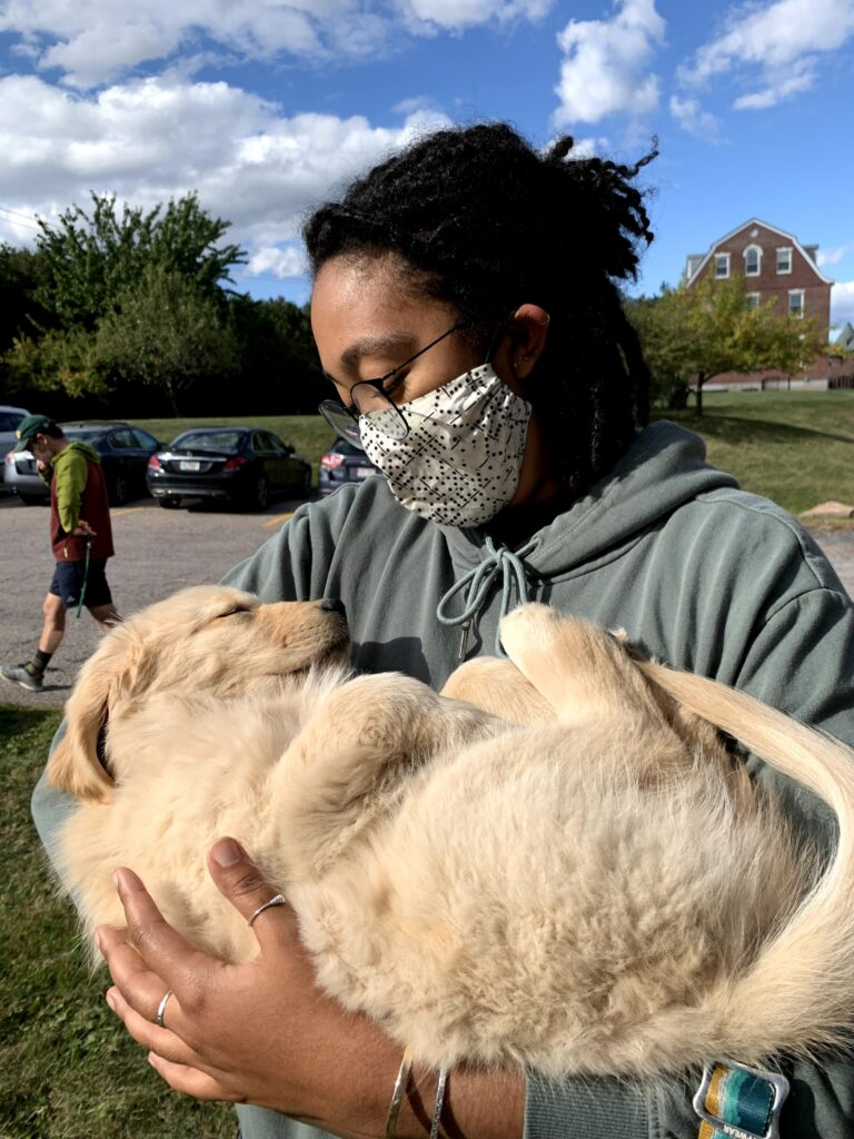 Woman wearing a mask and holding a dog