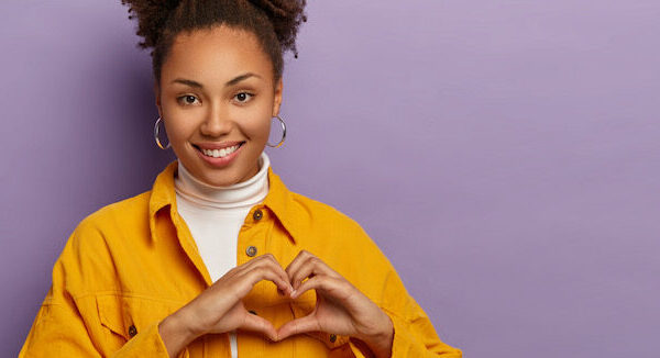 Woman making a heart with her hands wearing a yellow shirt