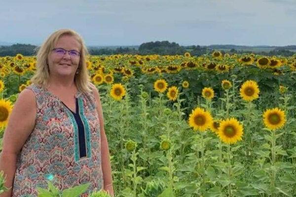 Kim Harrington standing in a field of sunflowers