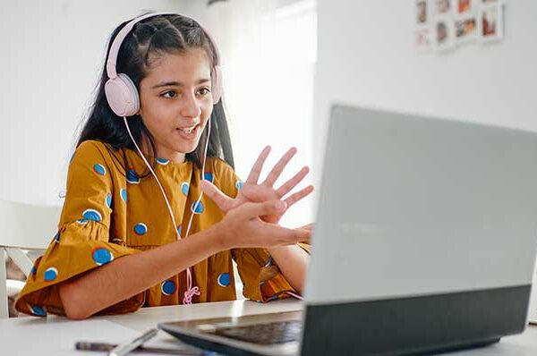 Teenage girl with headphones and laptop having online school class at home