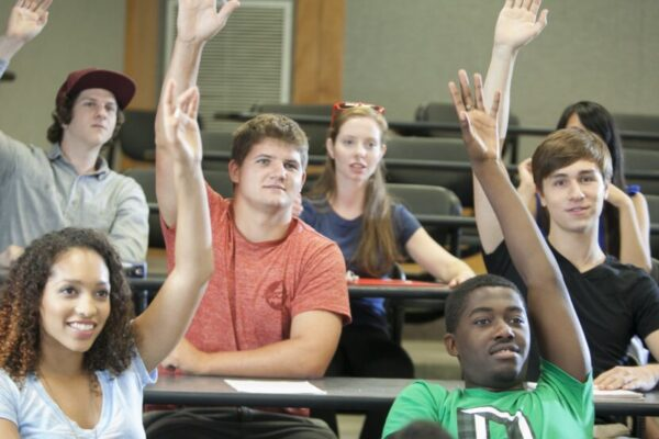 Students in a classroom raising hands