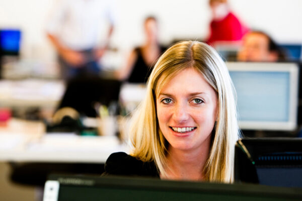 Woman smiling behind a computer