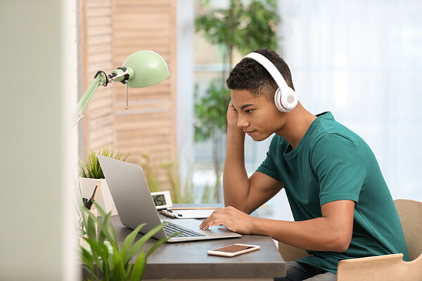 Student working on laptop with headset