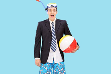 Man in a suit jacket wearing a swimsuit holding a beach ball