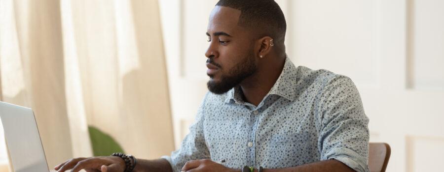 Man sitting at desk studying using computer