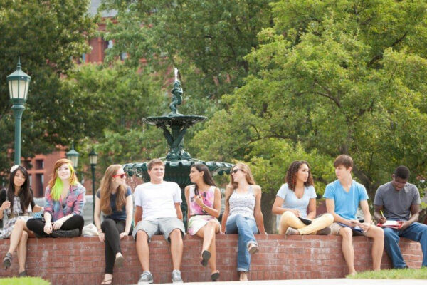 Students sitting around a fountain